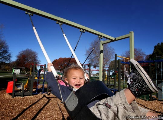 Korurangi Morehu, 2, Flaxmere, playing on the swings at Flaxmere Park, Flaxmere, Hastings, in the cool but sunny winter weather photograph