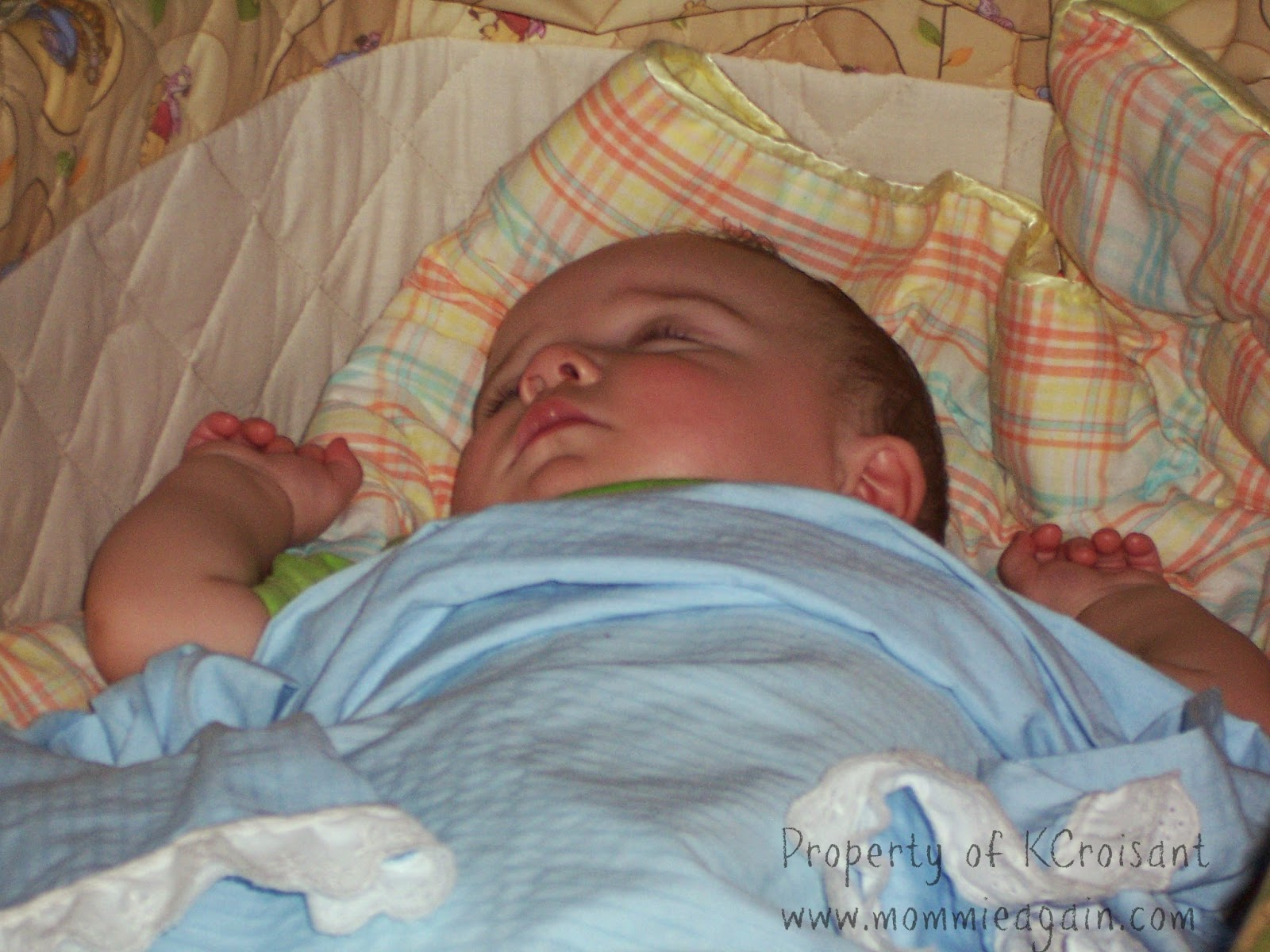 Baby boy laying on his back asleep in bassinet.