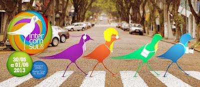 A imagem tem a logo marca do Intercom Sul 2013 aplicada à esquerda, numa foto, que simula uma famosa capa dos Betous, com pássaros atravessando a rua em cima da faixa de pedestres cada qual com um aparato eletrônico como: fones de ouvido, máquina fotográfica, óculos e bolsa.