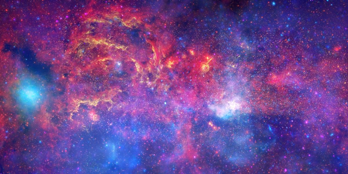 Центр нашей галактики Млечный путь в рентгеновском (синий), инфракрасном (красный) и видимом (желтый) диапазонах. Яркое белое пятно правее и ниже центра — Стрелец А*, сверхмассивная чёрная дыра.