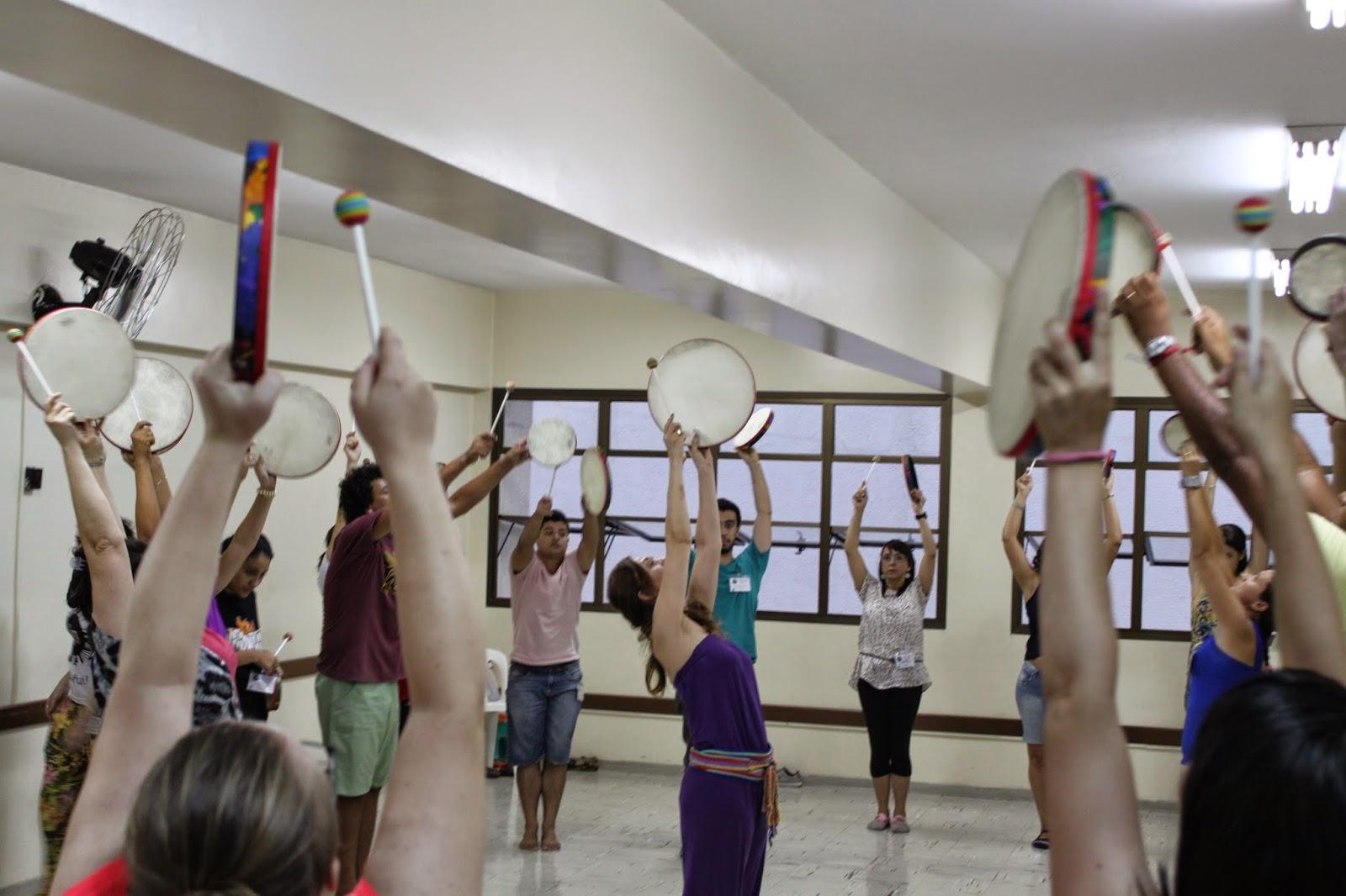 Descrição da Foto: Participantes estão em pé, com os braços esticados para cima, tocando o tambor.