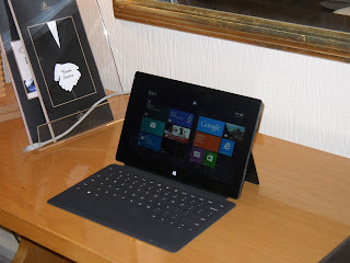 The Microsoft Surface sitting on a hotel desk, near a Room Service menu