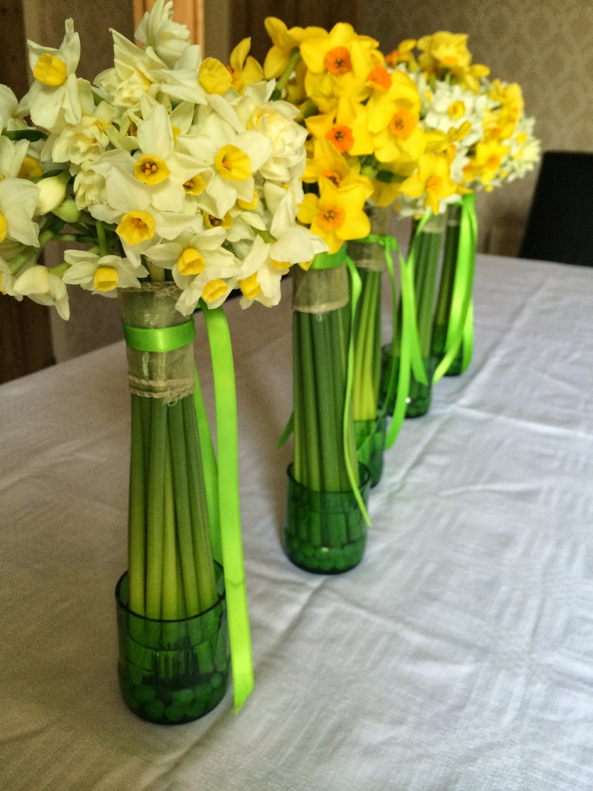 Gorgeous scented British narcissi in recycled bottle vases