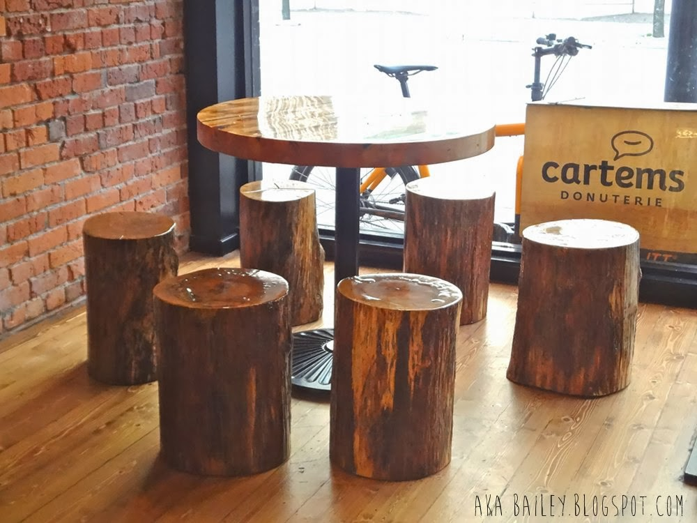 Table with log stools inside Cartems Donuterie in Vancouver