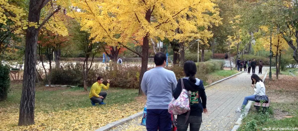 Coreano tomandose un selfie con baston delante de su novia