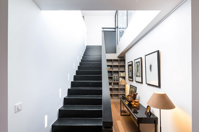 Simple black stairs side by side with pictures and a book shelf decoration.
