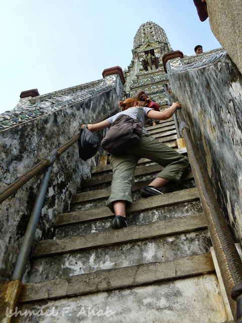 A tourist climbing up the steep steps of Wat Arun