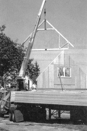 Figure 5.65 Roof trusses are typically lifted to the roof by a  boom mounted on the delivery truck. This is one  of a series of identical attic trusses, which will  frame a habitable space under the roof.