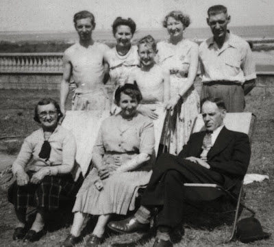 An out door group picture of eight people named in the caption.  Clementina is much older and Peter is a young boy, the ages of the others vary from 45 to late 20s.