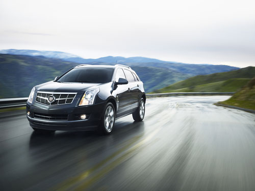 Front 3/4 view of 2011 Cadillac SRX on wet winding road