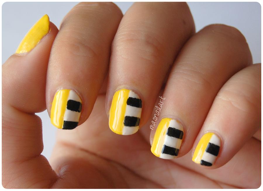 NOTD Uñas de moda amarillas con rayas blancas y negras.