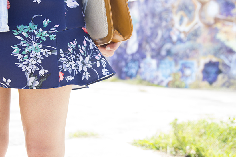 Fashion blogger Maria Copello is wearing a denim shirt from Madewell, necklace from Rapsodia, floral skirt from Zara and gold platform shoes from Zara.