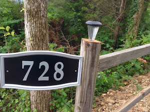 A close up of a fence light and the address plate.