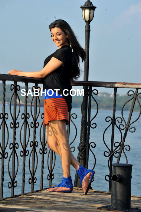 Kajal agarwal posing in a nice red skirt with an off shoulder black top and blue sandals.  - Kajal Agarwal in black top and red skirt