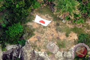 Foto udara Kyodo News menunjukkan bendera Jepang di salah satu pulau di kepulauan Senkaku/Diaoyu yang menjadi sengketa antara Jepang dan China di Laut China Selatan, Rabu (19/9). (Reuters)