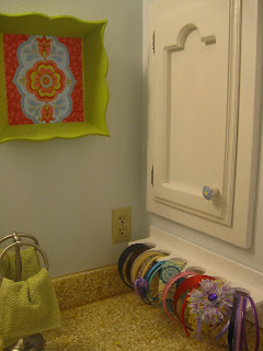 Craft organizer installed on bathroom wall, holding headbands