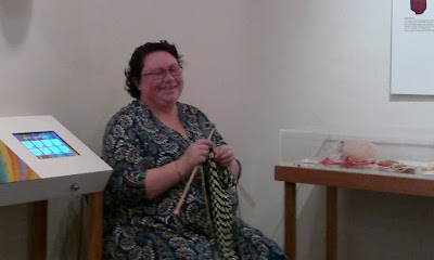 Between the display cabinets sits a woman (Cheryl) knitting with large wooden needles and a stripy fabric.