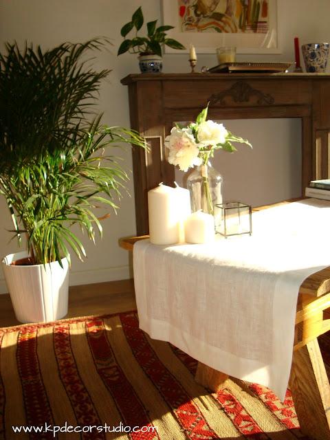 mesa de palet nordica decorada con velas y jarron de flores, manteles de lino natural para decorar mesa de cafe