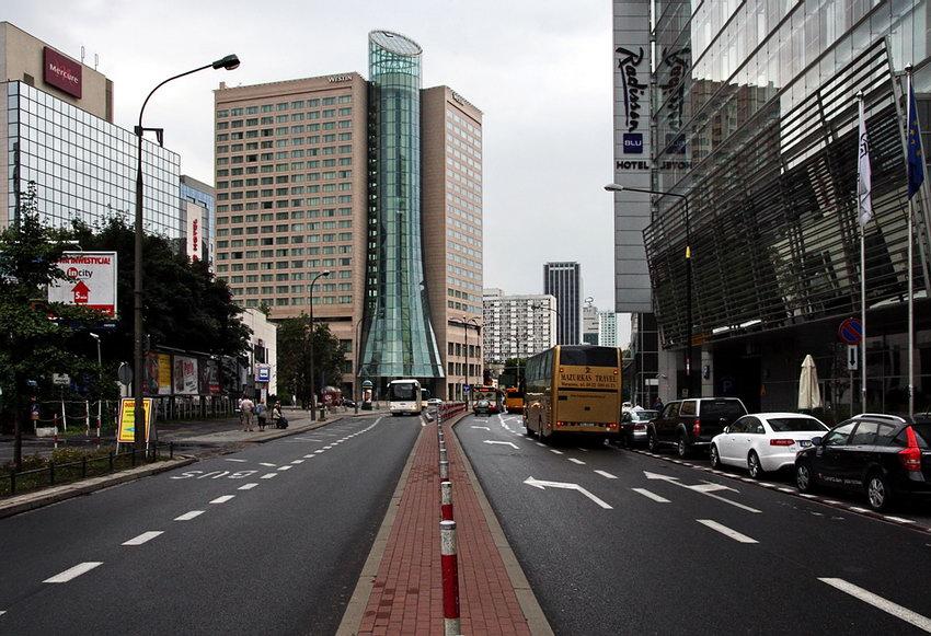 Foto tirada no e separador entre faixas, mostrando rua moderna com edifícios em vidro, sobretudo hotéis