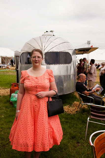 A fat lady in a coral 1950s dress in front of an aluminium caravan