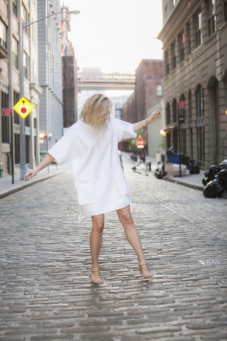 Messy blond hair, white boxy neoprene dress by Stefanie Biggel ss14, Vince Genna sandals in nude leather, cobblestone streets, Brooklyn