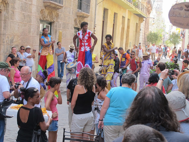 Street artists on stilts dancing and playing music for the visitors in Habana Vieja. Note the lady in the foreground selling small triangles of puff paste filled with guava jam.