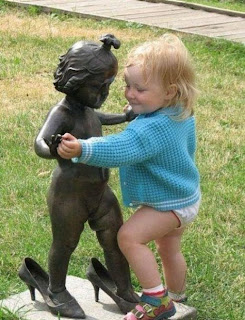 funny picture: dancing child with a statue