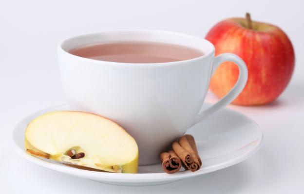 Xícara de chá, com uma fatia de maçã  e pau de canela no pires e uma maçã inteira no fundo.