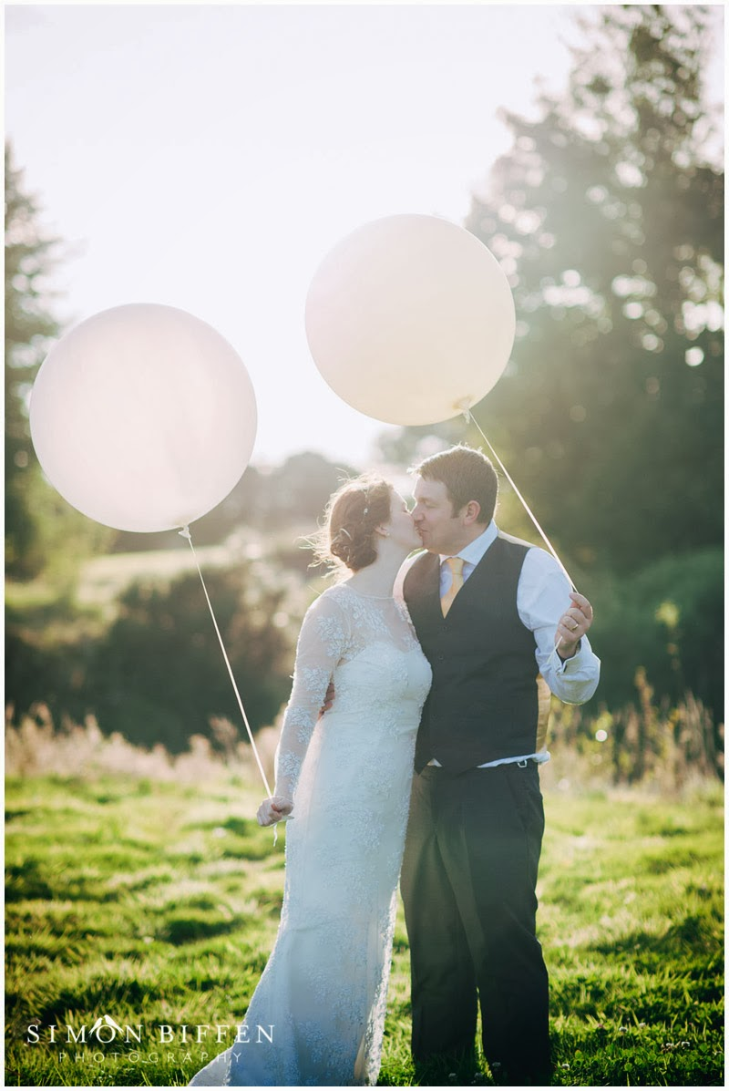 Bride and Groom kiss with balloon at Trevenna Cornwall