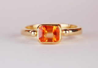 Simple ring with an emerald cut orange sapphire in a bezel setting
