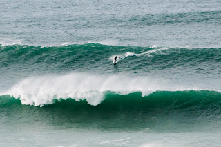 Surfer riding big waves in Newquay Cornwall