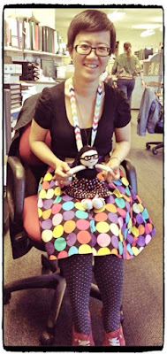 Little Colourful Teacher with Kwokkie Doll on her lap. They are both dresed in the same outfit of a black top with a polka-dotted skirt.