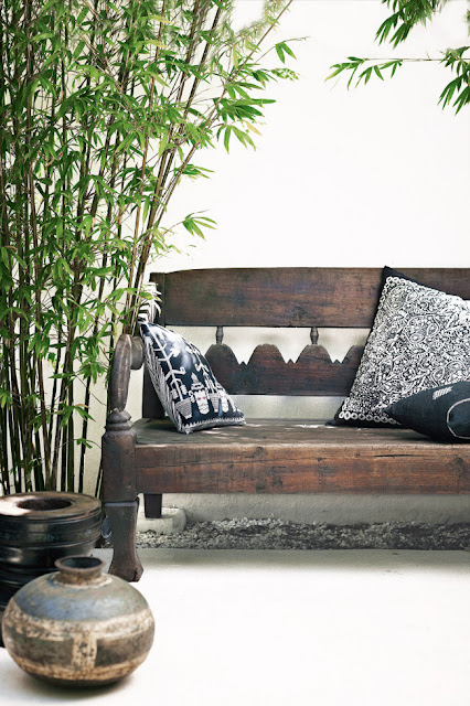 Patio with outdoor bench, navy blue and white pillows, bamboo, and two bowls
