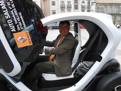 El alcalde alejo Riñones sonriente,  en un coche electrico