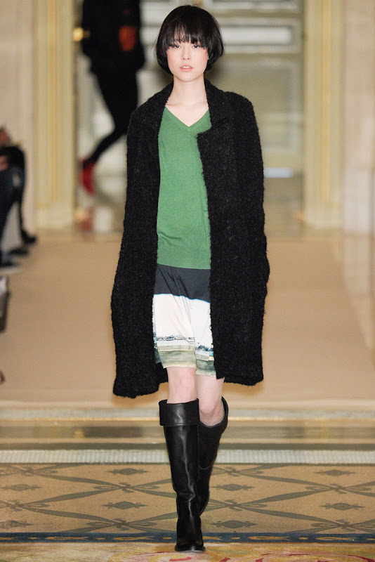 model from Agnes B.'s Fall 2011 Ready to Wear show. She's wearing knee high black boots, a slightly oversized green sweater, a white skirt with green stripes at the bottom and a long black jacket