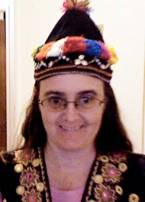 Cynthia Parkhill wearing black pointed hat with a multi-colored red, yellow, orange, blue and white pom-pom on the tip. Solid pom-poms in similar colors and a scallop pattern of shells ring the base of the hat. Also visible, the shoulders of a black vest decorated with small round mirrors inside yellow and pink circular embroidery designs.