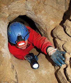 hombre dentro de un túnel con guantes, casco y linterna