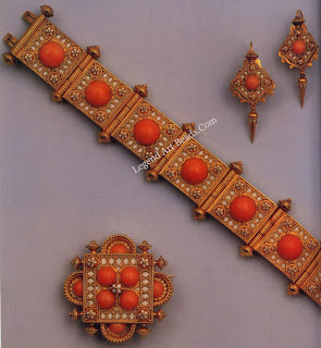 A matching bracelet, brooch and earring of coral set in gold and decorated with filigree enamel. The set was cased for Hancock`s and probably dates from the 1870s.