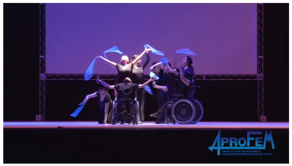 Descrição da Foto: Intérpretes estão no centro do palco, alguns de pé, uma ajoelhada e dois na cadeira-de-rodas. Eles estão com lenços azuis em uma das mãos dançando em posições diferentes.  Estão sobre luz um foco centro de luz branca.