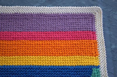 Tricot placemat in a rainbow of coloured stripes with a white herringbone stitch border.
