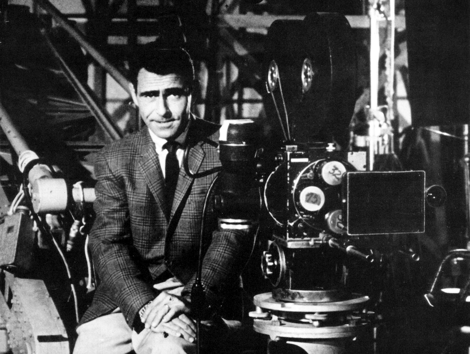 Rod Serling from Twilight Zone sits next to  a camera. B/W photo.