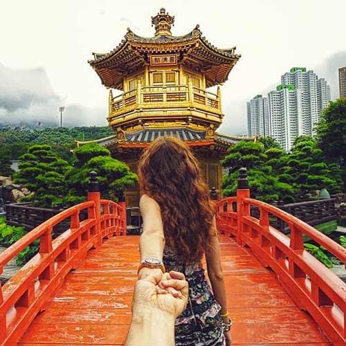 Fotografia em que se vê uma moça de costas, puxando pelas mãos o fotógrafo. Eles estão em uma ponte com um templo oriental ao fundo, no final da ponte. Só se vê a mão do fotógrafo e a namorada de costas.