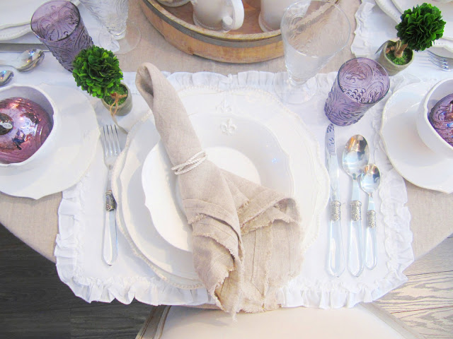 Close up of place setting with lavender glass, linen napkin, white placemats and silverware