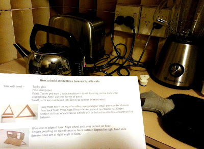 A set of kit instructions in front of a kettle and hot water bottle on a kitchen bench.