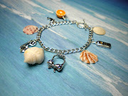 A pretty dolphin charm, and a sweet half orange complete this Florida . (florida seashell charm bracelet )