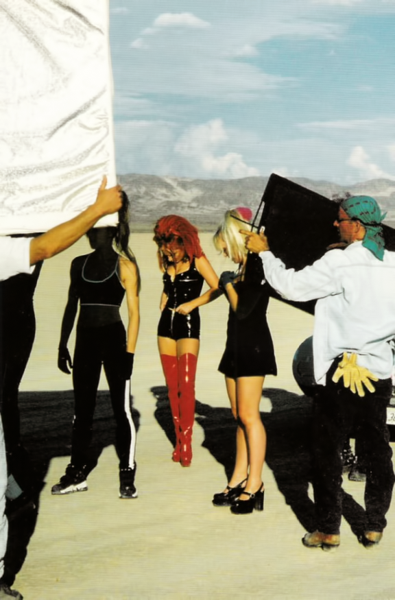 "The Spice Girls behind-the-scenes on set of their music video for ""Say You'll Be There"", Mojave Desert - September 1996. Candid, Beautiful! Chunky platform many-janes, Baby Spice, Little Black Dresses, Ginger Spice in Latex Leather in tall red boots, Sporty Spice as a techno-warrior in the shadows!"