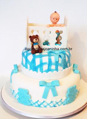 Bolo decorado chá de bebê, com o bebê no bercinho, ursinho de pelúcia e decoração em  xadrez azul e branco com lacinhos e patch work de ursinhos com barrado xadrez.