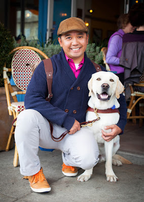 JR smiles while kneeling down with his arm around his guide dog Griff (yellow Lab) in front of a cafe in San Francisco.