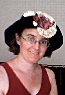Cynthia Parkhill wearing black hat with the brim folded up in front and a large pink and white flower attached to it.