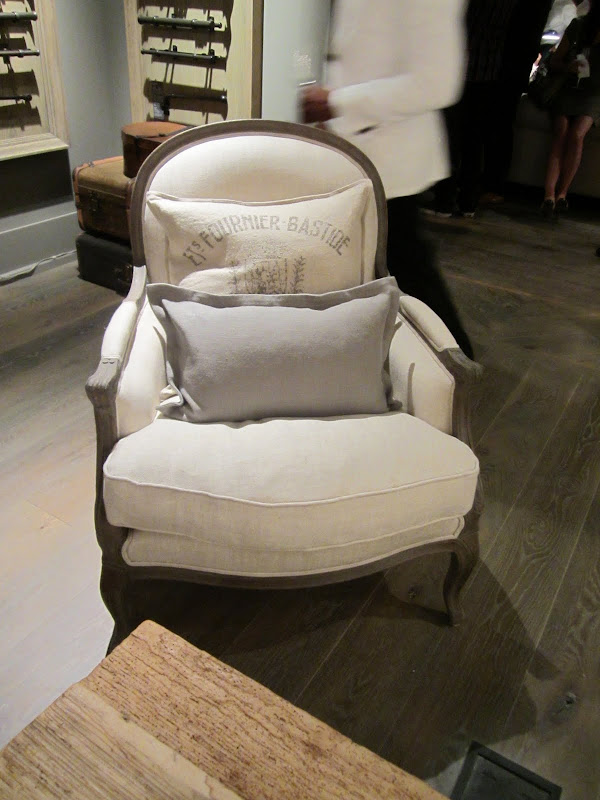 "Taupe upholstered armchair with a large accent pillow that say ""Ets Fournier Bastide"" and a small grey rectangular pillow on a painted wood floor"